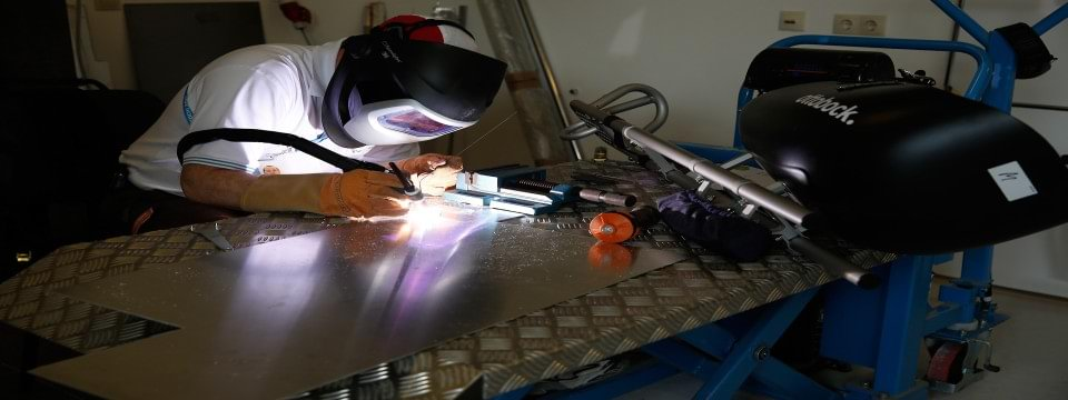 Ottobock Director of Sales and qualified welder Hughes Myner carries out detailed welding to repair a sledge hockey sled at the Sochi 2014 Winter Paralympic Games.