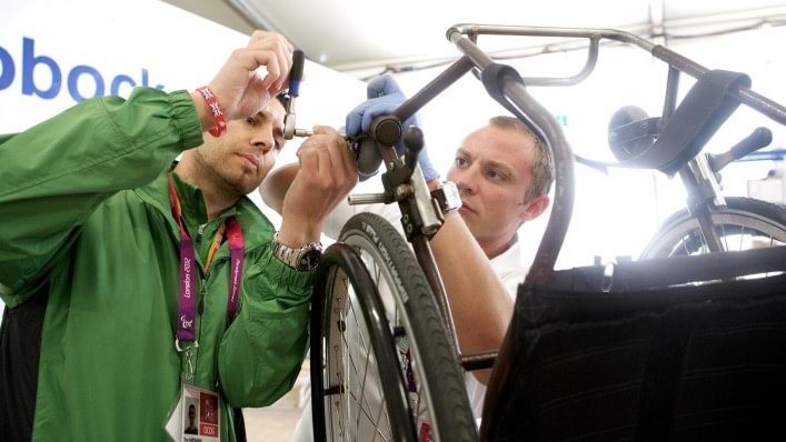 Ottobock technicians work together to repair a wheelchair in the technical service repair centre in the Athletes' Village at the London 2012 Paralympic Games