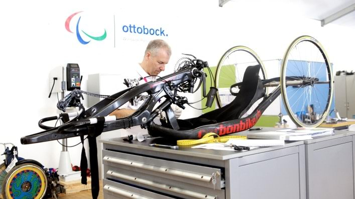 An Ottobock technician repairs a handcycle in the technical service repair centre in the Athletes' Village at the London 2012 Paralympic Games