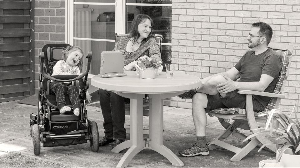 Girl with cerebral palsy sits with her parents and the Kimba Neo rehab buggy in the garden.