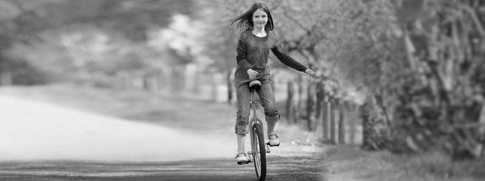 A girl rides a unicycle with an arm prosthesis for children.