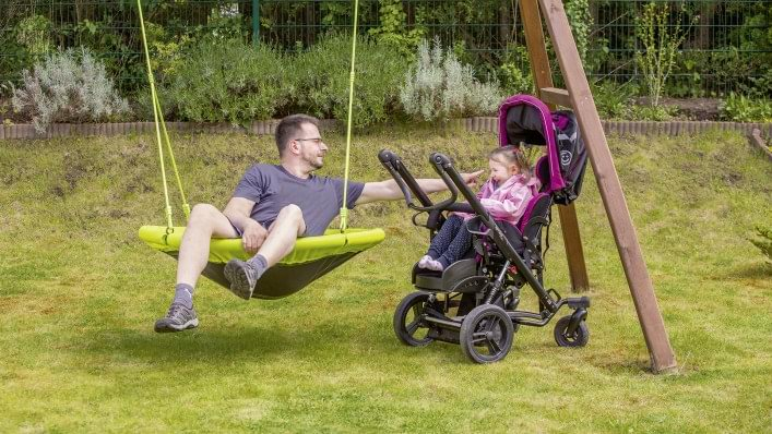 Girl in a rehab buggy plays with her father