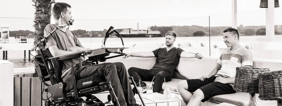 Ottobock's Juvo power wheelchair – scene: a wheelchair user and two friends on a dock near the water