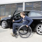 A man getting into his car from a wheelchair