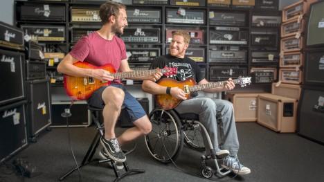 Thomas grający na gitarze elektrycznej w swoim Voyager Evo z przyjacielem.