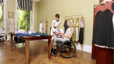 Nina siedząca w swoim Voyager Evo, wybierająca tkaniny w studio.