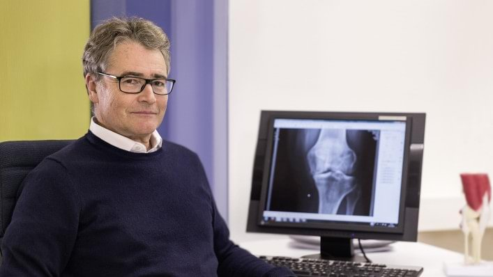 Doctor smiling confidently in front of computer screen with medical imaging of osteoarthritis