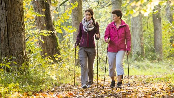 Woman wearing Agilium Freestep hiking through the woods with a friend