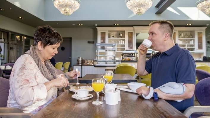 Stephan having breakfast with his girlfriend and using the H200 Wireless forearm orthosis.