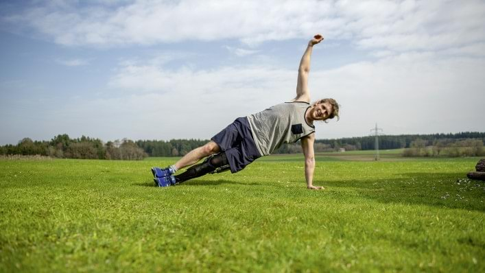 Man yoga stretching outside while wearing C-Brace