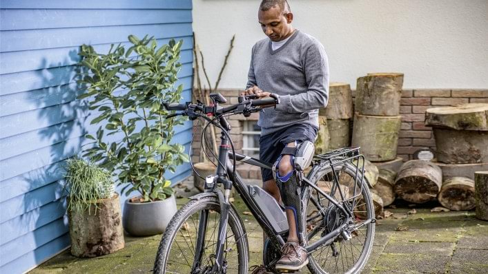 Melvin sits on his bicycle. He is wearing his computer-controlled C-Brace® orthotronic mobility system. He is holding his mobile phone, which shows the adjustment app on the display