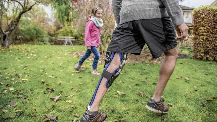 Melvin wears his computer-controlled C-Brace® KAFO. He is playing football with his niece.