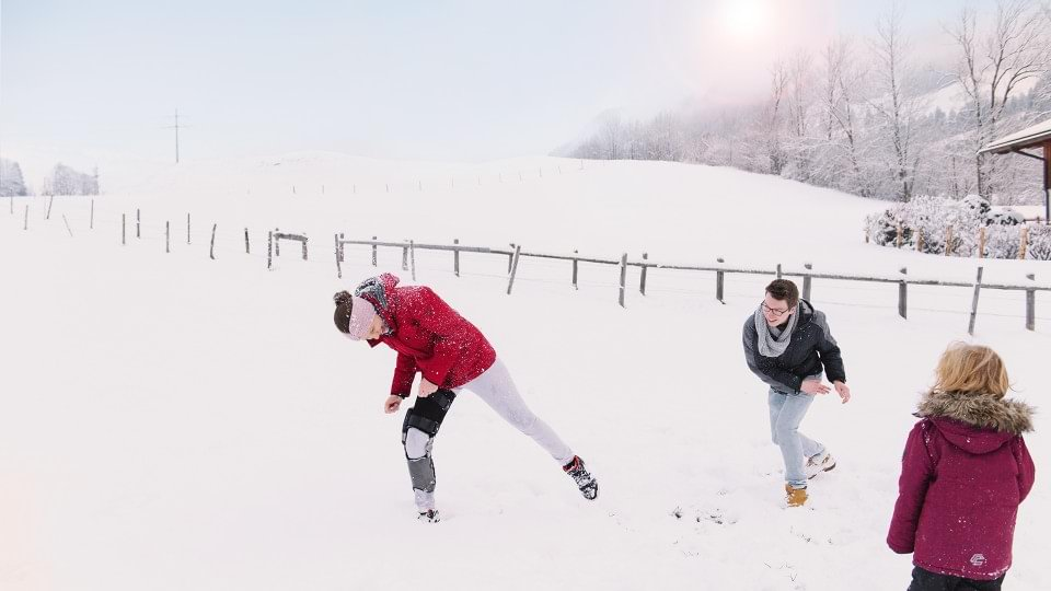 Denise wears the C-Brace® and plays in the snow with her children.