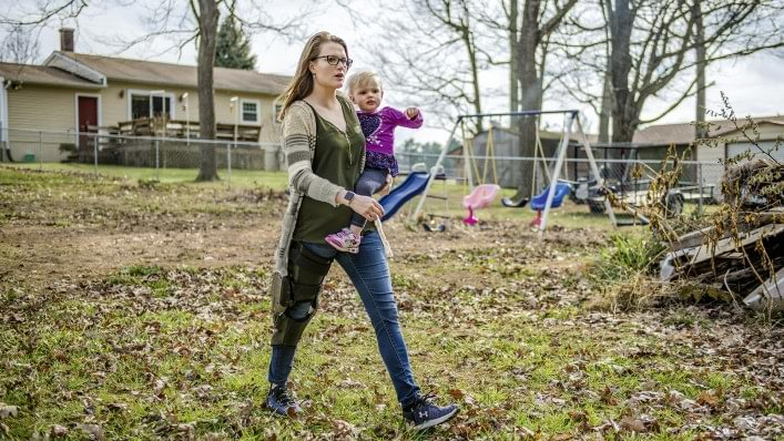 Hannah wearing her C-Brace and pushing her child on a swing