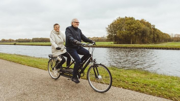 C-Brace® wearer Marjan rides tandem with her husband.