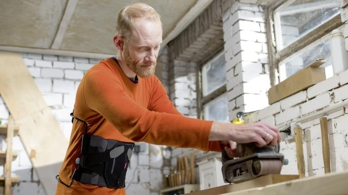 Volker with the Dyneva back orthosis working with wood in his workshop.
