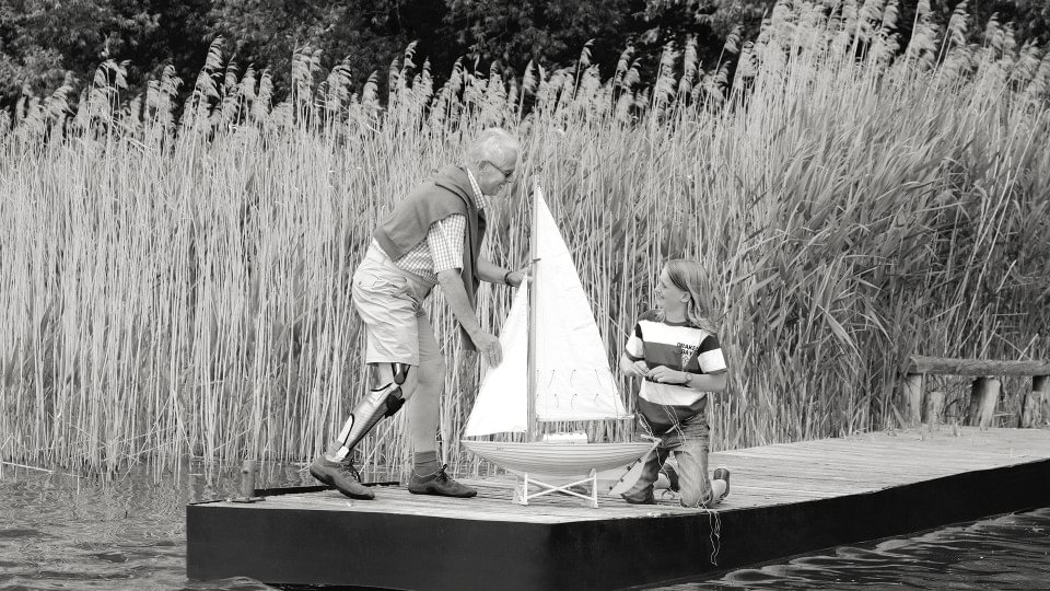 Peter with the E-MAG Active orthosis system playing on the dock with his grandchild