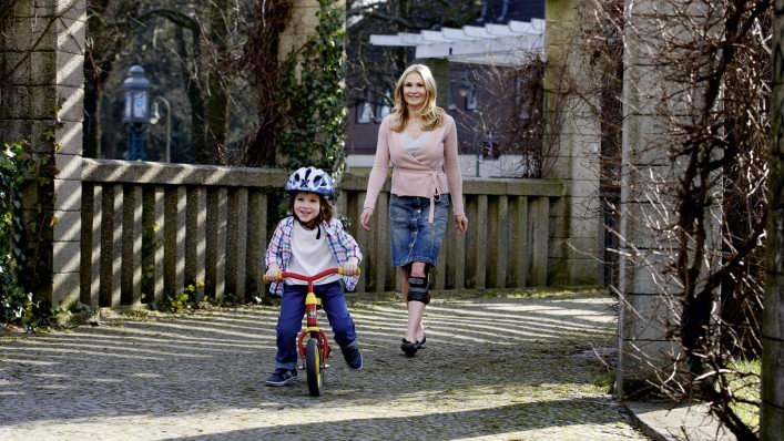 Mother with Genu Arexa knee orthosis taking a walk with her son
