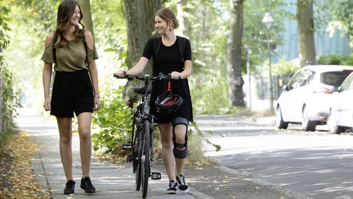 User with the Genu Arexa knee brace biking with her friend