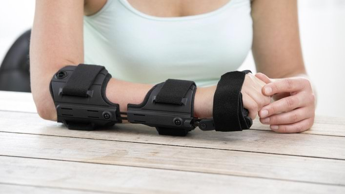 Woman easily putting on Omo Neurexa brace with one hand