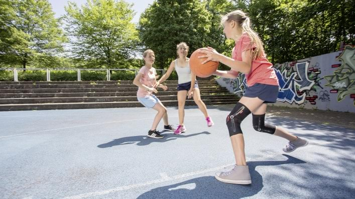 A girl plays basketball with Patella Pro.