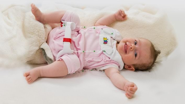 Tilda wears the Tubingen hip flexion and abduction orthosis as she sleeps in her mum's arms.