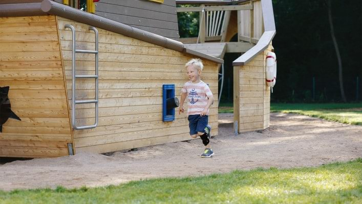 Child running across a playground. He is wearing the WalkOn Reaction junior, a dynamic ankle-foot orthosis from Ottobock, on his left leg