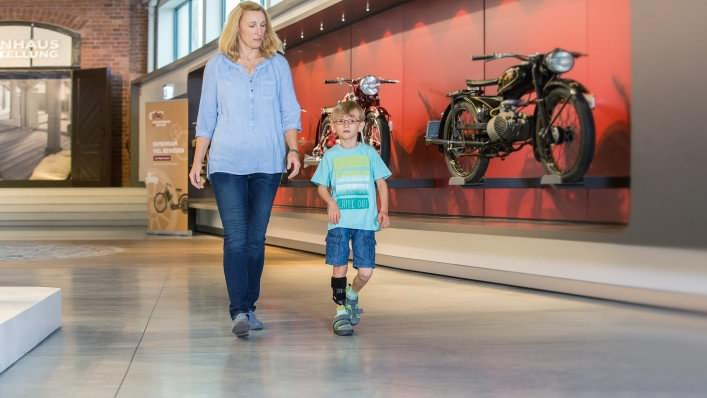 Mother and son visiting a motorcycle exhibition. The boy is wearing the WalkOn Reaction junior, a dynamic ankle-foot orthosis from Ottobock