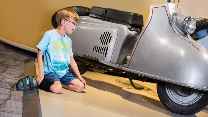 Boy looking at a scooter. He is wearing the WalkOn Reaction junior, a dynamic ankle-foot orthosis from Ottobock