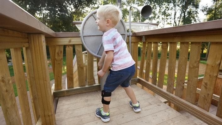 Child playing on a playground. He is wearing the WalkOn Reaction junior, a dynamic ankle-foot orthosis from Ottobock, on his left leg