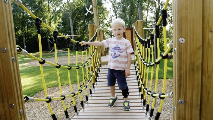 Boy crossing a hanging bridge on a playground with the WalkOn Reaction junior, a dynamic ankle-foot orthosis from Ottobock