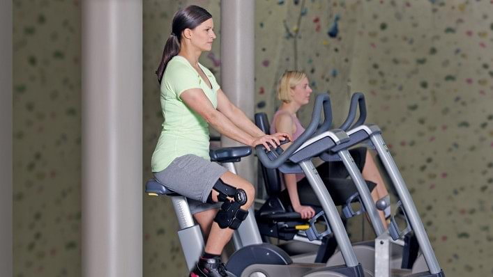 Young woman with the Xeleton knee orthosis on an exercise bike at the fitness studio