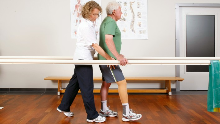 A physiotherapist conducts gait exercises at the parallel bars with a prosthesis wearer.