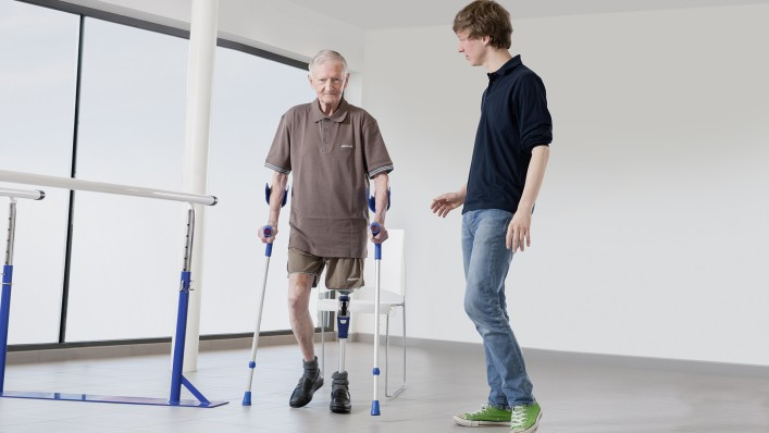 An amputee walks with two walking aids in the presence of his technician.