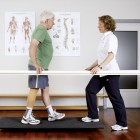 The therapist performs a balance exercise at the parallel bars with a prosthesis wearer.