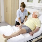 A therapist is standing at the hospital bed of a leg amputee, massaging his residual limb.
