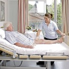 The therapist performs initial mobilisation exercises with the amputee at the hospital bed.