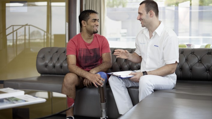 Prosthesis wearer in conversation with an O&P professional.