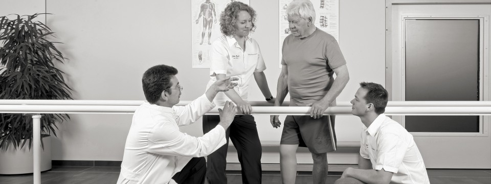 User standing by parallel bars with technicians and a doctor.