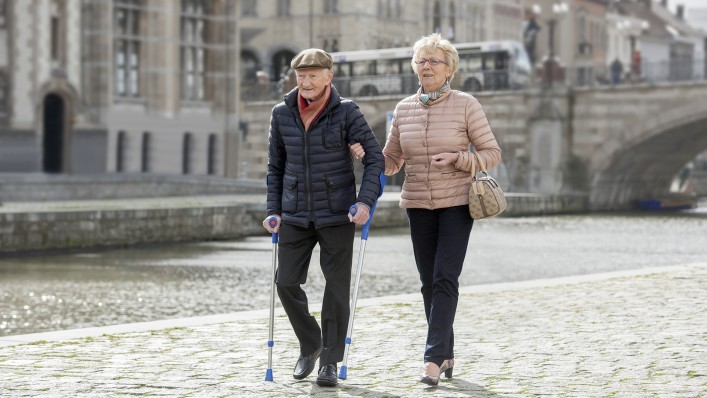 With his Terion K2 prosthetic foot, an elderly user on a walking aid and supported by his wife takes a short walk through the city centre.