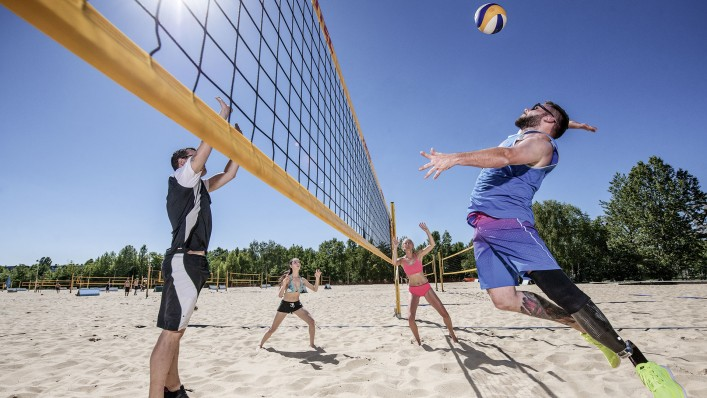 With his Challenger prosthetic foot, Alex plays volleyball in the sand with three friends.