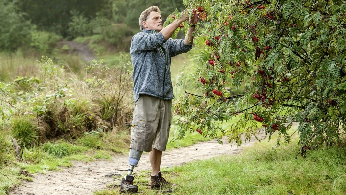 With his Meridium prosthetic foot, Hans stands at a bush and picks berries.