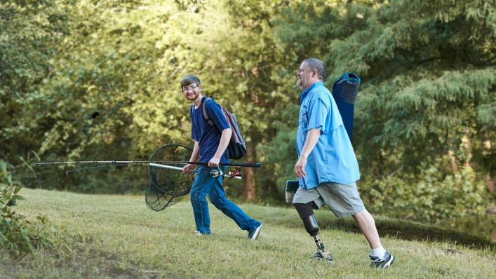 After fishing, Martin walks up a grassy hill with his Taleo prosthetic foot together with his son.