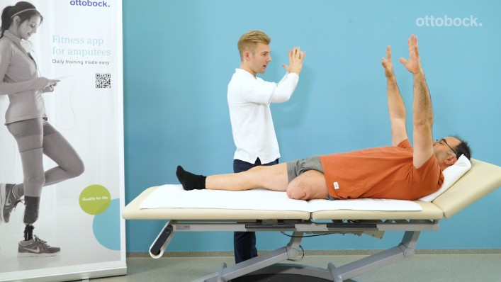 The therapist performs mobility exercises with a leg amputee at the hospital bed.