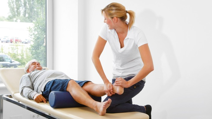 Physiotherapist does rehabilitation exercises with forefoot amputee on a bench