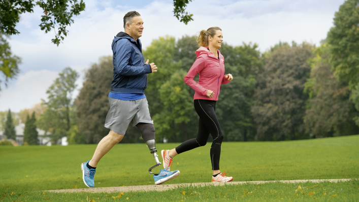 User of the Quickchange adapter for changing prosthetic feet running in the park with his partner.