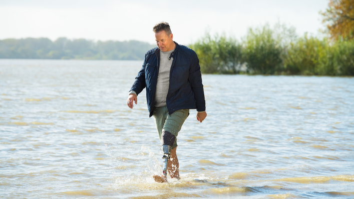 User of the Quickchange adapter for changing prosthetic feet walking in the water along a riverbank.