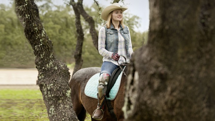 Through the trees, a cowgirl can be seen sitting on her horse.