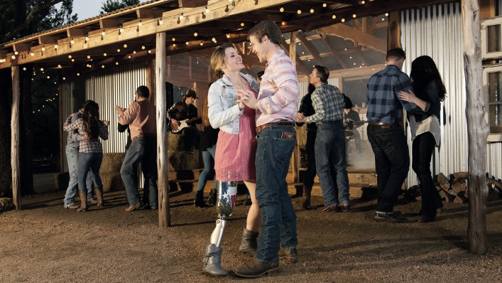 : A couple laughs and dances; she wears a C-Leg. A band and people dancing can be seen in the background.