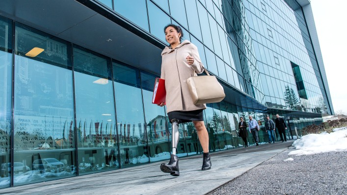 A user with the C-Leg leg prosthesis walking to work outside a glass-fronted office building.